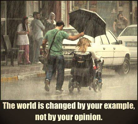 "Man holding an umbrella over a woman in a wheelchair. ""The world is changed by your example, not by your opinion."