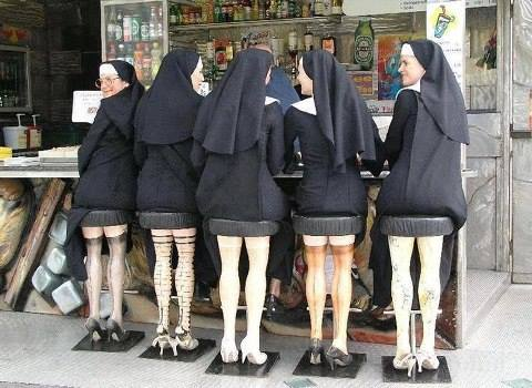 Six nuns sitting on stools at a lunch counter. The stools are decorated with mannequin legs in sexy stockings.