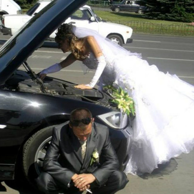 Photo: New bride in her wedding dress repairing her automobile while husband sits on the curb.